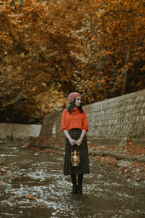 Woman in Red and Black Coat Standing on River