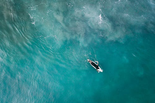 Surfer on board in vivid blue reservoir