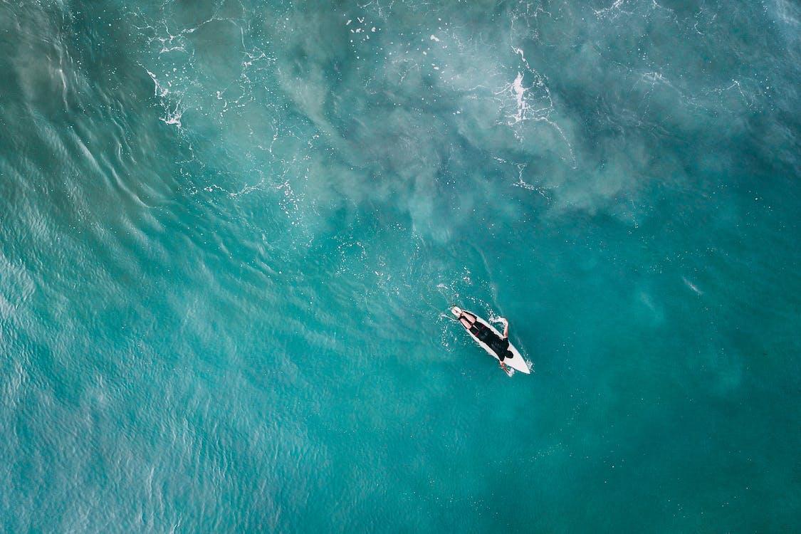 Surfer on board in vivid blue reservoir