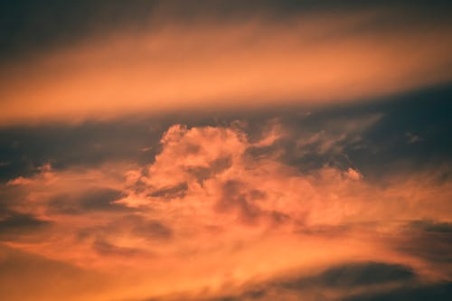 Cloudy sky lightened with bright rays of sunset