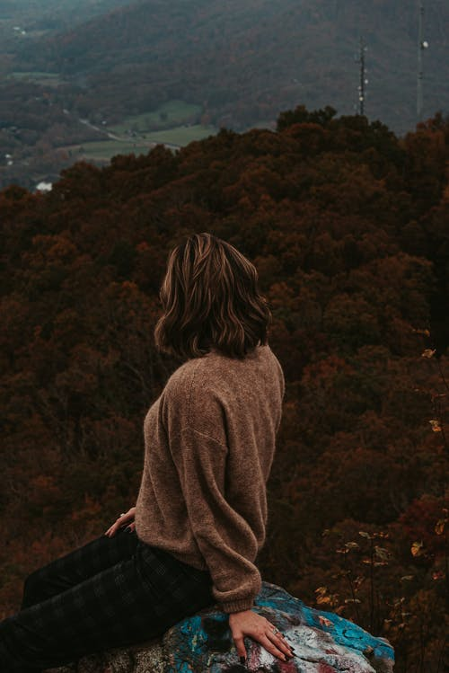 Unrecognizable woman sitting on hilltop and admiring verdant hilly terrain