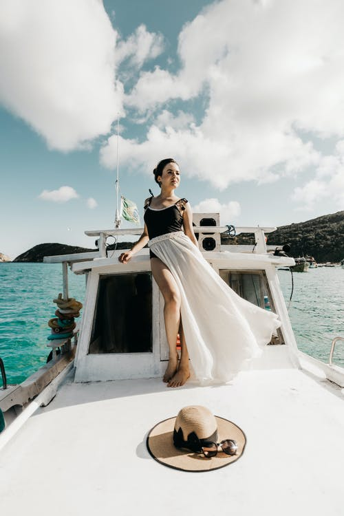 Woman in White Dress Sitting on White Boat