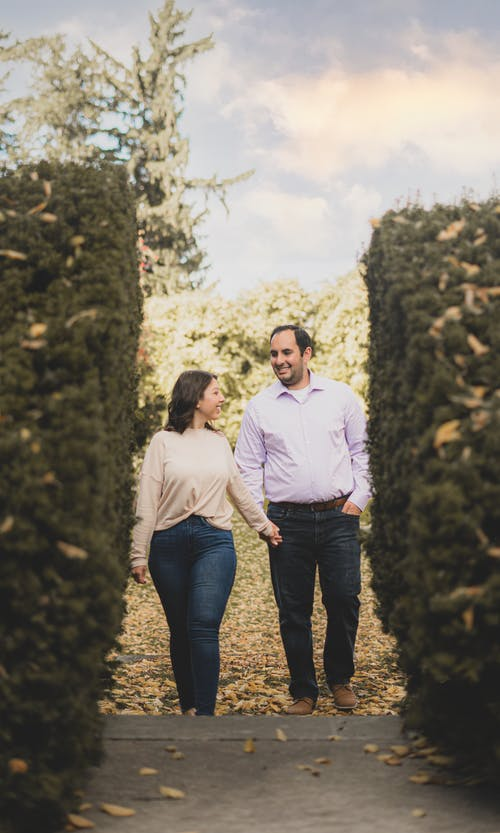 Full body of positive couple talking and promenading in park with green bushes under cloudy sky