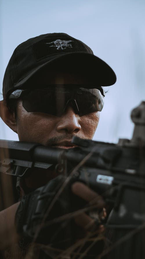 Close-Up Shot of a Man with Military Sunglasses Holding an Assault Rifle