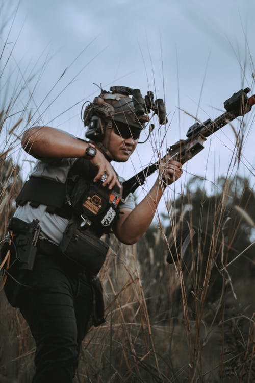 A Man with Military Vest Holding an Assault Rifle