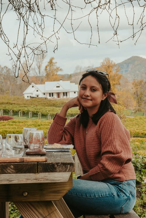 Young woman resting near vineyards in mountainous countryside