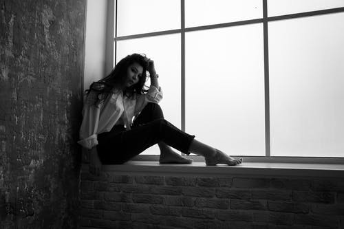 Black and white full body side view of pensive young barefoot female sitting on windowsill and looking at camera