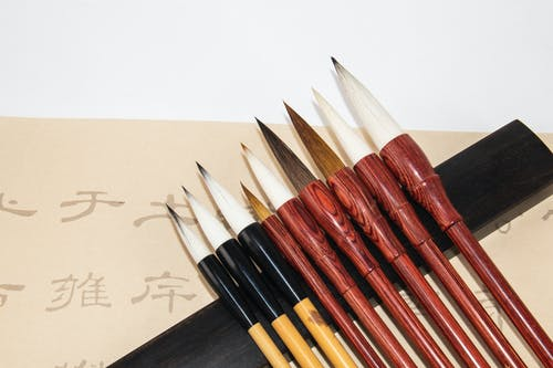 Set of calligraphy brushes near paper with hieroglyphs