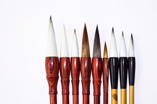 Contemporary calligraphy brush pens of different sizes with soft spiky tips and shiny bamboo shafts