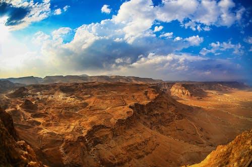 Spacious deserted rough terrain under blue sky