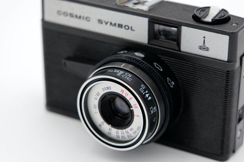 Close-Up Shot of a Black Analog Camera on a White Surface