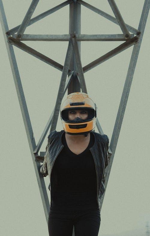 Anonymous woman in biker helmet near metal tower
