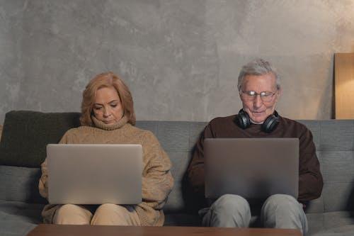Woman in Brown Sweater Sitting on Brown Sofa Beside Man in Black Sunglasses