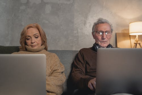 Elderly Man And Woman Sitting On Couch Using Laptop Computers