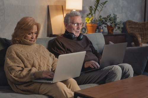 Man and Woman Sitting on Couch Using Macbook