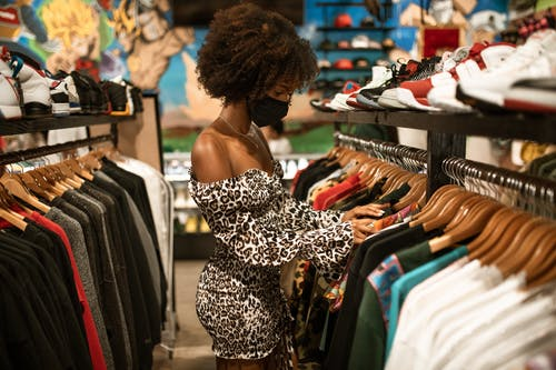 Woman in Black and White Leopard Print Spaghetti Strap Dress Standing in Front of Clothes Display