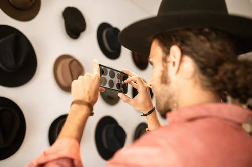 Close-Up Shot of a Person Taking Photos of Hats
