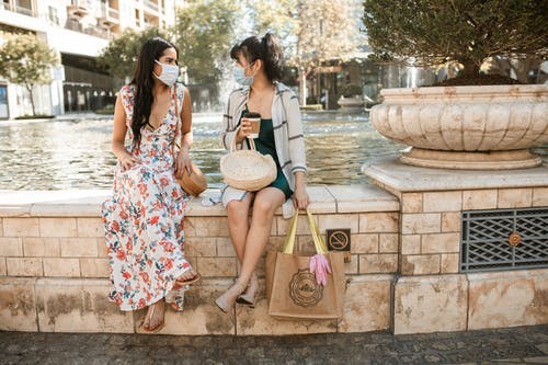 Two Women Meeting Outdoors Wearing a Facemask