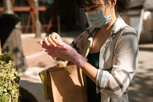 Mulher De Camisa Branca Com Botões Segurando Uma Caixa De Papelão Marrom