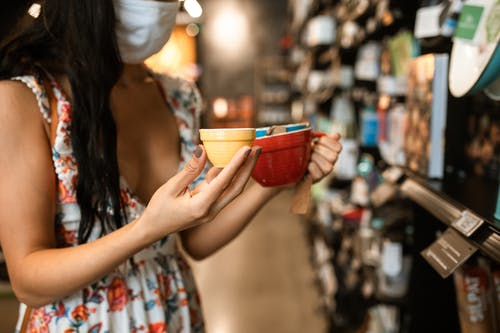 Woman Holding A Red and Yellow Ceramic Cups
