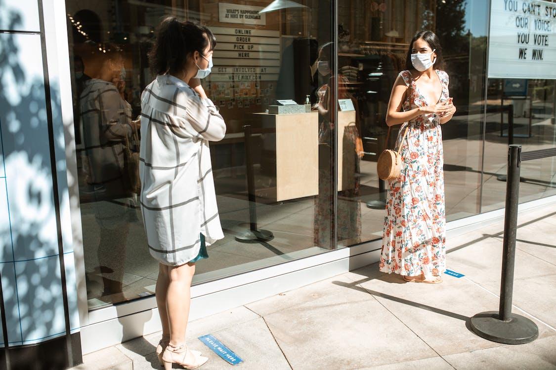 Woman in White Coat Standing Near Glass Door