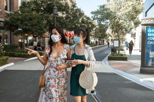 Two Brunette Women Walking On The Street and Looking Around