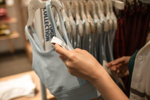 Person, Die Weißen Plastik Kleiderbügel Hält
