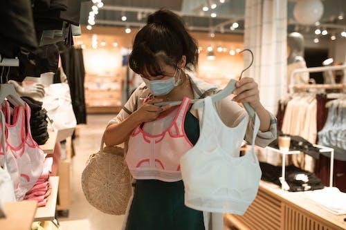 白色和粉红色的背心,拿着白色吊袋的女人