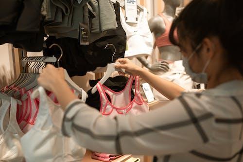 拿着粉红色和白色手提袋的白色长袖衬衫的女人