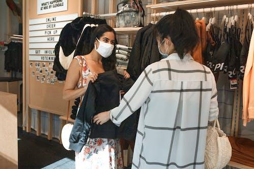 站在黑色长袖的女人旁边的白色和黑色条纹长袖衬衫的女人