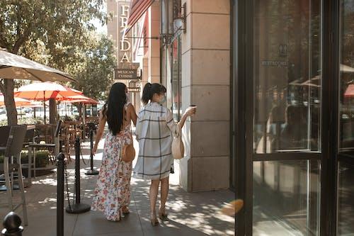Donna In Abito Floreale Bianco E Rosso In Piedi Accanto A Donna In Camicia Bianca