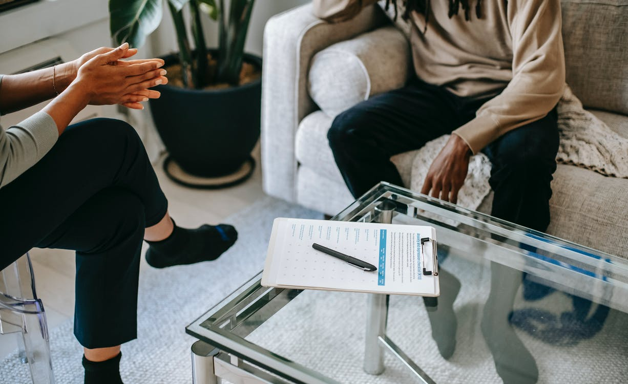 Crop anonymous African American man in casual clothes sitting on sofa and talking to female psychologist during psychotherapy session in modern studio