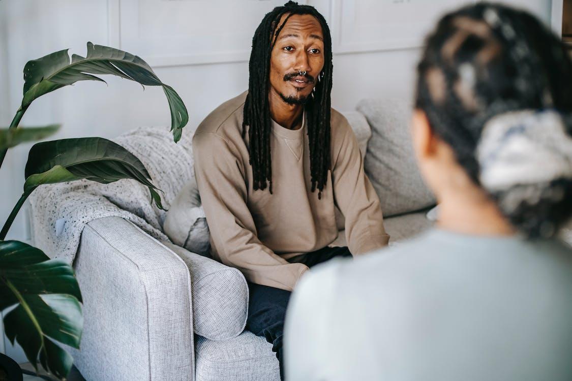 Positive black man talking to female therapist