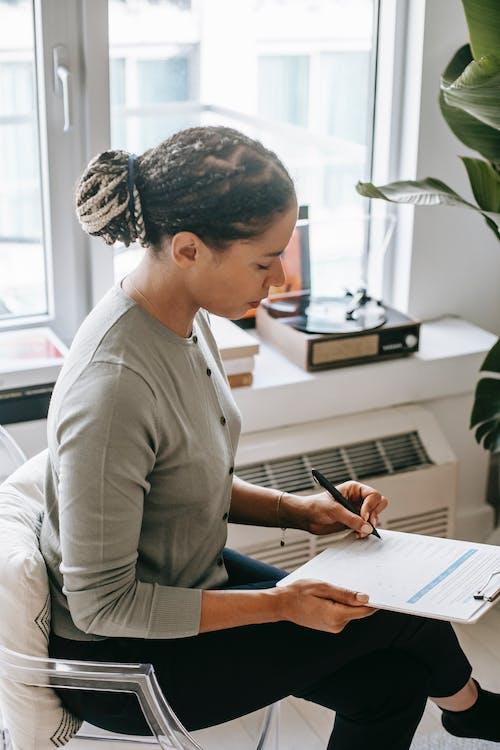 Focused ethnic woman writing on clipboard