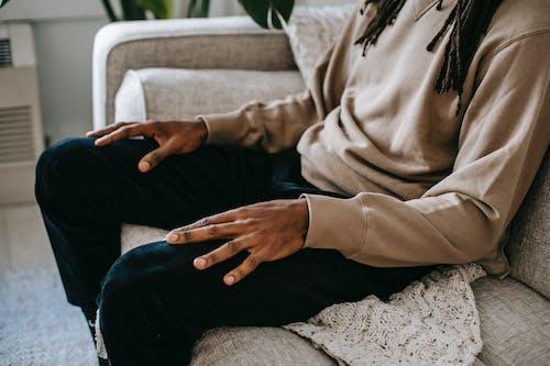 Crop ethnic man sitting on sofa