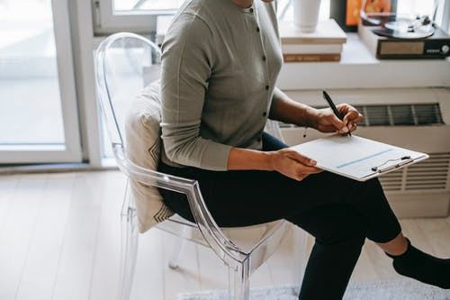 From above of unrecognizable female psychologist with crossed legs taking notes on clipboard while filling out questionnaire during psychotherapy appointment in cozy office