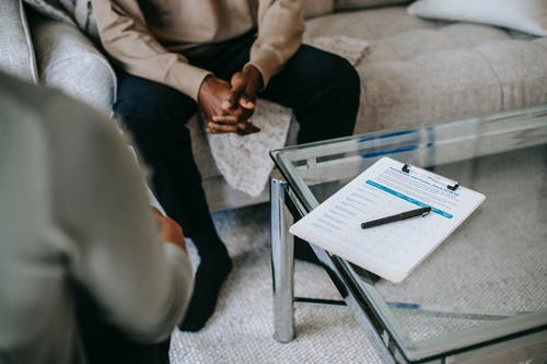 From above of unrecognizable ethnic male patient with clasped hands sitting near anonymous psychologist in office with glass table and clipboard with notes