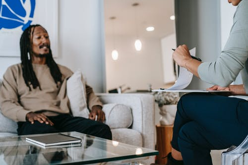 African American male with dreadlocks sitting on sofa in front of unrecognizable female therapist with clipboard during psychotherapy appointment in office