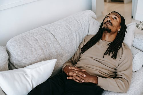Pensive black man lying on couch