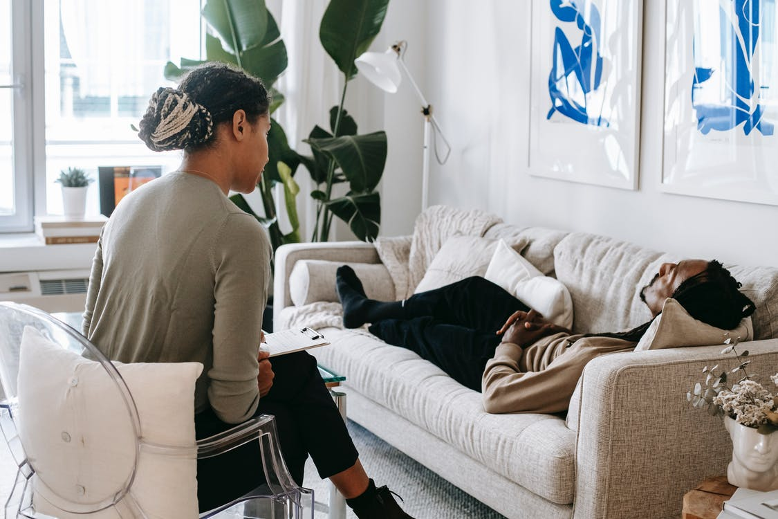 Ethnic female therapist with clipboard sitting near male client lying on couch with clasped hands during psychotherapy session in cozy office