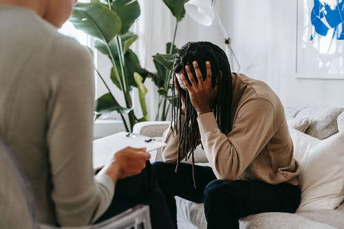 Stressed black man with dreadlocks in psychological office