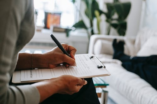Unrecognizable ethnic female therapist taking notes on clipboard while filling out form during psychological appointment with anonymous client lying on blurred background