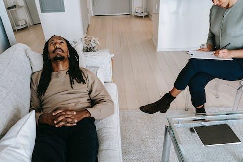 Black man lying on sofa in psychological office