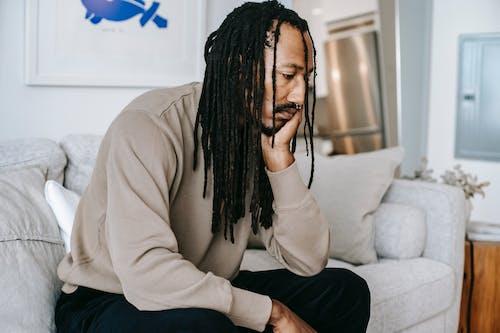 悲傷的黑人男子坐在沙發上