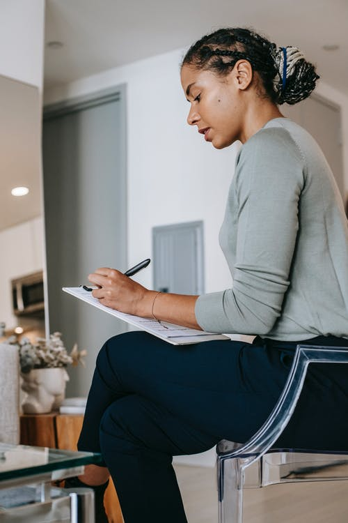 Serious black woman taking notes in living room