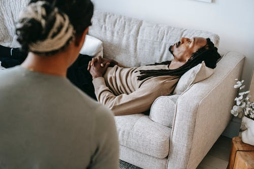 Black man lying on sofa during psychotherapy