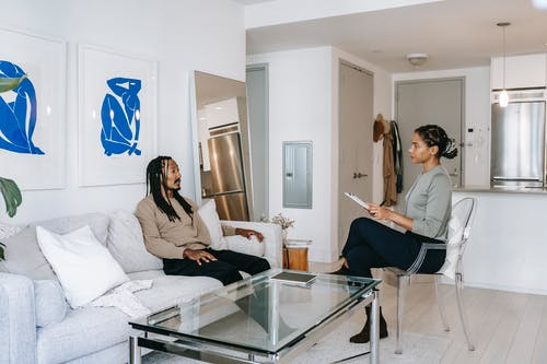 Concerned African American male in smart casual clothes sitting on comfortable sofa and sharing problems with empathetic female consultant in contemporary psychotherapy center
