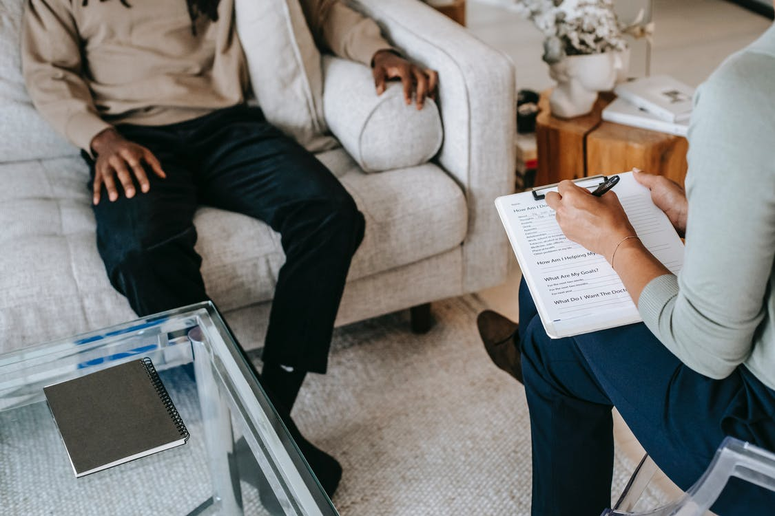 From above crop African American male in casual clothes sitting on comfy couch and answering professional female consultant questions in modern psychotherapy office