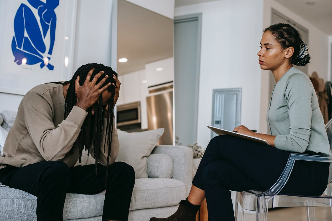 Overwhelmed black man discussing problem with female psychologist