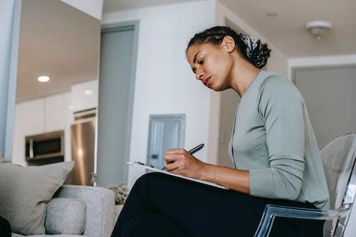 Intervistatore Femminile Etnico Concentrato O Psicoterapeuta Che Prende Appunti Negli Appunti